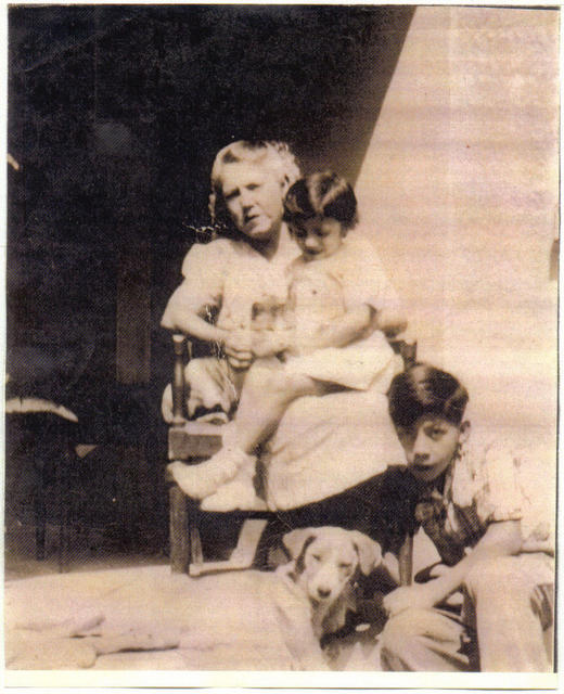 Eva on Grandmother's lap (Dad's Mom) and Uncle Raul playing with dog